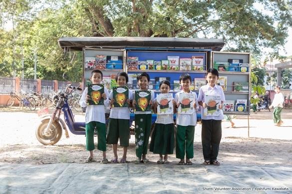 ミャンマーの移動図書館バイクの前で絵本を手にした子どもたち