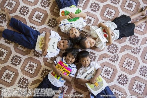 クメール語の翻訳シールが貼られた日本の絵本を手にしたカンボジアの子どもたち