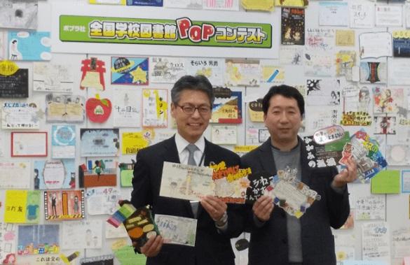 ポプラ社賞作品を持つポプラ社代表取締役社長の千葉均さん(左)とPOP王賞作品を持つ内田剛さん(右)(背景の作品は、一次選考通過作品)